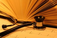 Book and stethoscope. On a EKG printout Royalty Free Stock Photo
