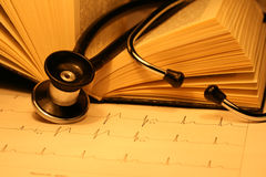 Book and stethoscope. On a EKG printout Stock Images