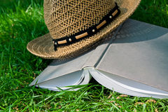 Book and straw hat on grass Royalty Free Stock Photos