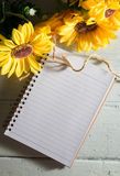 Book with sun flowers on table. Royalty Free Stock Photography