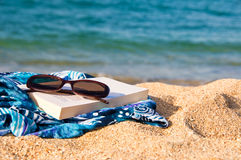 Book, sunglasses on a beach Royalty Free Stock Images