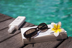 Book and sunglasses, blue water Royalty Free Stock Photo