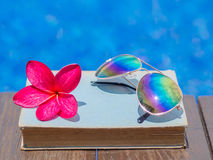 Book and sunglasses, blue water background,. Summer and tropical travel destinations concept Royalty Free Stock Images