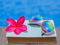 Book and sunglasses, blue water background,. Summer and tropical travel destinations concept Royalty Free Stock Photo