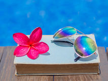 Book and sunglasses, blue water background, Royalty Free Stock Photo