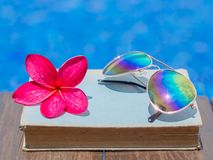 Summer and tropical travel destinations concept. Book and sunglasses, blue water background, summer and tropical travel destinations concept Stock Photo