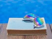 Summer and tropical travel destinations concept. Book and sunglasses, blue water background, summer and tropical travel destinations concept Royalty Free Stock Image