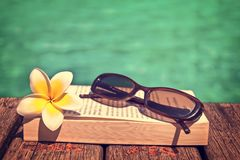 Book and sunglasses, blue water background. Vintage process Royalty Free Stock Photos
