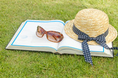 Book and sunglasses with straw hat Royalty Free Stock Photography
