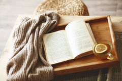 Book and sweater. Warm knitted sweater and a book on a wooden tray Royalty Free Stock Image