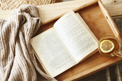Book and sweater. Warm knitted sweater and a book on a wooden tray Stock Photography