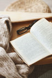 Book and sweater. Warm knitted sweater and a book on a wooden tray Royalty Free Stock Photography
