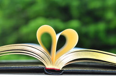Book on Table With Golden Pages Forming Heart Shape Royalty Free Stock Image
