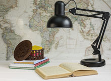Book and table lamp. On a background map of the world stock photos