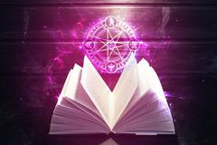 Book on the table out comes light and magic sign Royalty Free Stock Image
