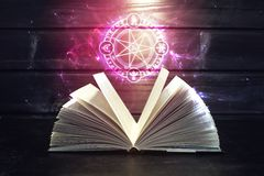 Book on the table out comes light and magic sign. Open magical book with pages like a fan is on the table out comes a colorful light and magic sign. The concept Stock Images