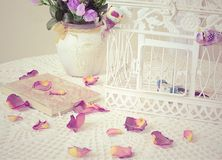 The book on a table with rose petals. The book on a table with rose-petals Royalty Free Stock Photography