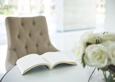 Book on table with white rose flower in living room. Blank book on table with white rose in living room interior decoration background Royalty Free Stock Images