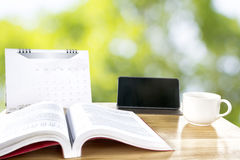 Book, Tablet, Calendar and white cup on wooden table. Green nature blurred in background Stock Image
