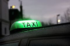 Paris taxi sign in rainy day. Book a taxi early in the morning in the parisian suburbs. Take the taxi or a direct shuttle bus that operates between the hotel and stock image