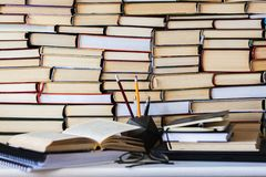 Book, textbook and glasses in library, stack piles of literature text archive, bookshelves in school study class room background f stock photography