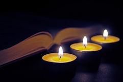 Book with three candles. Three candles with open book Royalty Free Stock Photos