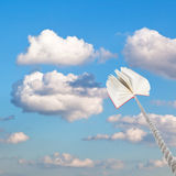 Book tied on rope soars into little white clouds Royalty Free Stock Image