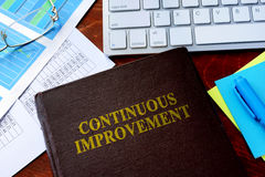 Book with title continuous improvement. Stock Photography