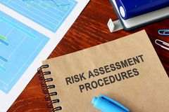 Book with the title Risk assessment and financial data. Book with the title Risk assessment and financial data on a desk stock photography