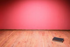 Book to lie floor red wall Stock Photography