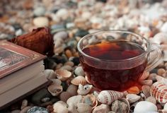 Book and transparent glass cup with tea standings. Transparent cup of tea standing on the shells and book with rose bookmark Royalty Free Stock Photo