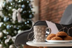 Book with treat on table and Christmas tree stock images