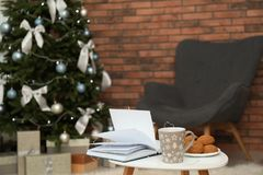 Book with treat on table and Christmas tree royalty free stock photo