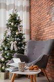 Book with treat on table and Christmas tree royalty free stock image