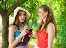 Book & Two Beautiful happy smiling women outdoors Royalty Free Stock Photo