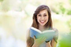 book utomhus att läsa kvinnabarn Royaltyfria Bilder