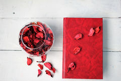The book and vase with rose petals. Red Book and a bowl of rose petals on white table Stock Photo