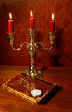 Book, watch and candelabra, focus on watch Royalty Free Stock Photography