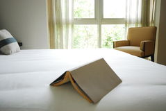 Book on white bed. A book on the edge of a neatly made white bed Royalty Free Stock Photos