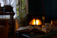 Book Beside White Cup on Black Table With View of Fireplace in the Background during Daytime Stock Images