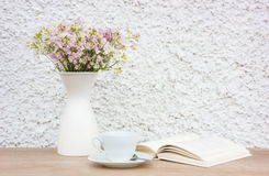 Book, white cup and vase with flowers Royalty Free Stock Image