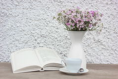 Book, white cup and vase with flowers Royalty Free Stock Photography