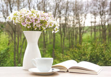 Book, white cup and vase with flowers Stock Images