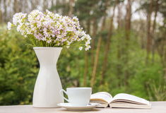 Book, white cup and vase with flowers Royalty Free Stock Images