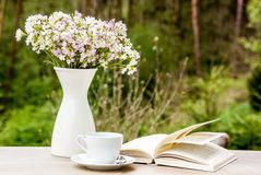 Book, white cup and vase with flowers Royalty Free Stock Photos