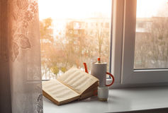Book on the window. Book with a cup on a windowsill with red shine Stock Image