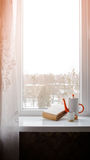 Book on the window. Book with a cup on a windowsill with red shine Royalty Free Stock Photo