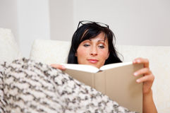 Book woman on couch Stock Image