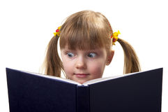 Book of wonders. Funny little girl wondering while reading a book over white background Royalty Free Stock Photo