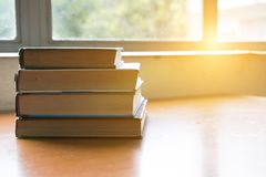 Book on wood table. textbook beside window. education, study con. Old book on wood table. textbook beside window. education, study concept Royalty Free Stock Photo